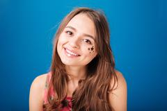 Pretty happy young woman with star shaped decoration on cheek Stock Photos
