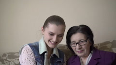 Girl and mature woman using a tablet, embracing, smiling, caring Stock Footage