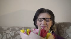 Old woman in glasses holding bouquet tulips, smelling, smiling Stock Footage