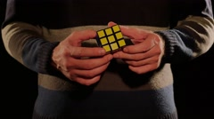 Close up shot of a man solving the Rubik´s cube, isolated on a black background - stock footage