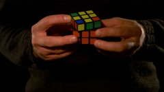 Close up footage of a man isolated on a black background solving a Rubik´s cube - stock footage