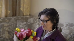 Mature business lady sitting, smiling, smelling the aroma of tulips. Slowly - stock footage