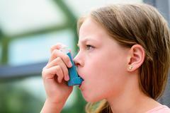 Girl having asthma using the asthma inhaler Kuvituskuvat