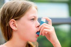Girl having asthma using the asthma inhaler Stock Photos