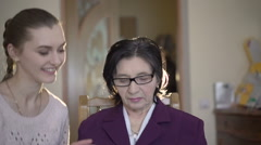 Mature woman in glasses sitting, using the tablet, girl coming to her in a room Stock Footage