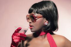 Retro 60s fashion african woman with sunglasses holding cocktail glass. - stock photo