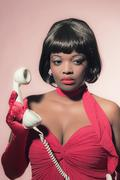 Retro 60s fashion african woman in red dress holding earpiece of telephone. - stock photo