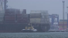 Container cargo ship leaving port with tug boat assistance in heavy snow weather - stock footage