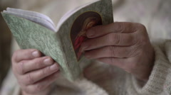 Prayer book in old woman's hands. Slowly Stock Footage