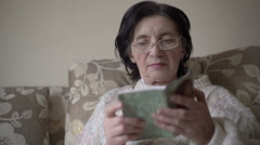 Old woman in glasses reading a prayer book on a sofa Stock Footage