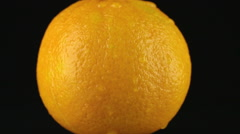 Drop of water flows down the skin of an orange Stock Footage