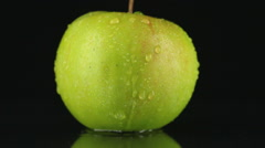 Drop of water flows down the skin of an green apple Stock Footage