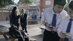 4K School boys looking at mobile phones outdoors in school playground Stock Footage