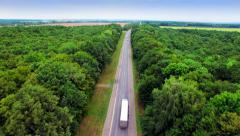 Stock Video Footage of Aerial view of the road through green forest.