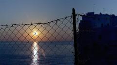 Broken fence sea dawn sun calm tungsten Stock Footage