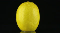 Drop of water flows down the skin of an lemon Stock Footage