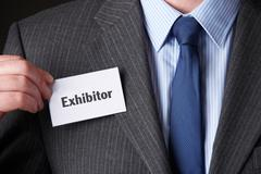 Businessman Attaching Exhibitor Badge To Jacket - stock photo