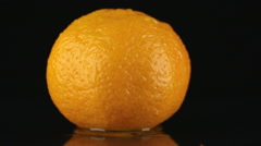 Drop of water flows down the skin of an mandarin Stock Footage