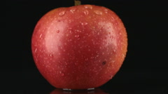 Drop of water flows down the skin of an red apple Stock Footage