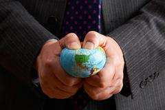 Businessman Squeezing Globe Over North America - stock photo