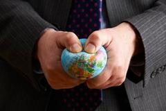 Businessman Squeezing Globe Over Europe And Africa - stock photo