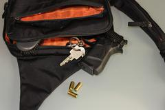 Carried concealed. Handgun and accessories falling from a woman's purse. Stock Photos