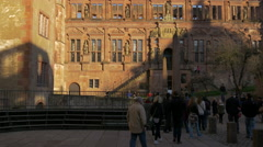 People walking towards a building filled with statues at Heidelberg Castle - stock footage