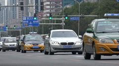 Heavy traffic drives through a commercial business district in Beijing, China Stock Footage