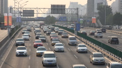 Heavy traffic drives over a busy highway in Beijing, China air pollution Stock Footage