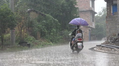 China extreme weather, heavy rainfall, motorbikes ride through village Stock Footage