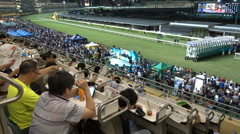 People gamble on the horse races in a stadium Hong Kong, China Stock Footage