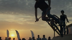 Silhouette Of Bmx Rider Against The Sunset While Performing tricks on a bike in - stock footage
