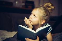 Girl reading a book and dreams - stock photo