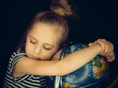 Beautiful girl hugs the globe and calmly asleep - stock photo