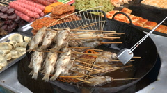 Frying fish skewers, street vendor, cheap food, popular snack, village in China Stock Footage