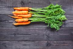 Ripe fresh carrots on a wooden background. Stock Photos