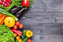 Background of wooden  black planks with fresh vegetables. Stock Photos