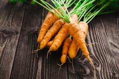Ripe fresh carrots on a wooden table in black. Stock Photos