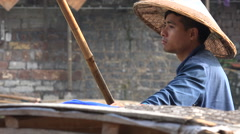 China tourism, local worker, conical bamboo hat, sad tired look in his eyes - stock footage
