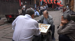 Chinese men play traditional chess in ancient restored village Fenghuang - stock footage