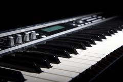 Synthesizer keyboard in shadow - stock photo