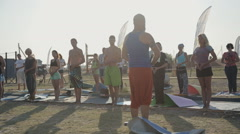 Stock Video Footage of Young People Are standing And Practicing Meditation with a yoga teacher on the