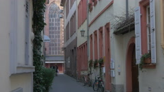 Couple walking on a narrow street close to Church of the Holy Spirit, Heidelberg Stock Footage