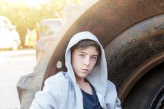 Stock Photo of portrait of a teenage boy leaning against a huge tire