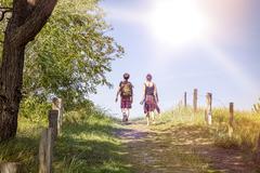 two teenager walking a path at noon - stock photo