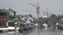 China contrast, ancient water town, bridge, looming construction cranes Stock Footage