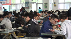 University students eat lunch, large cafetaria, school canteen, China education - stock footage