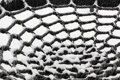 Snowy circular net of a rope swing Stock Photos