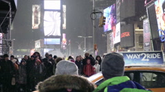 Snowing people waiting taxi driving across crosswalk Times Square winter NYC Stock Footage