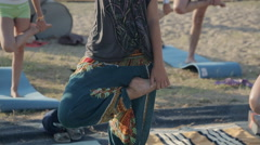 young girl doing yoga pose on a mat among other people on the coast - stock footage